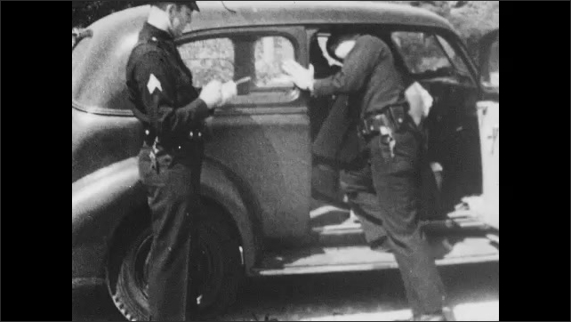 1940s: one officer taking notes while other officer searches car