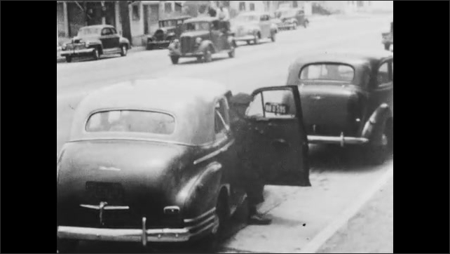 1940s: police officers pulling over car, officers get out of patrol car and walk to car they pulled over