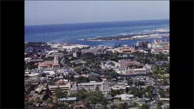 1950s: HAWAII: city settlement by ocean. View across city by sea. City buildings. Mountain in distance