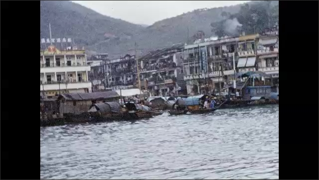 1950s: HONG KONG: village on water. Boats tied up a port. House boats on water.