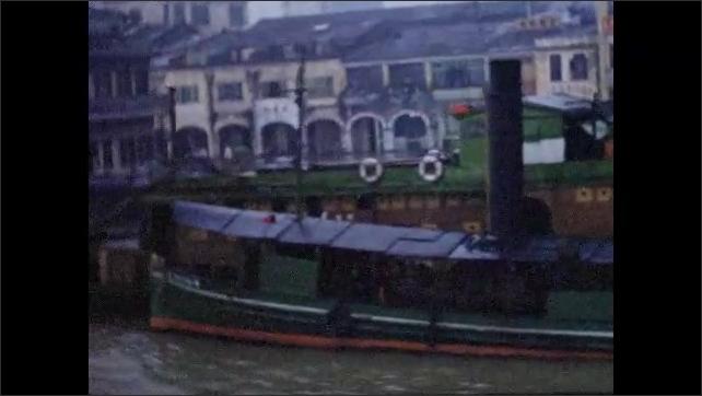 1950s: HONG KONG: view across water towards boats on moorings. Boats by town. Men row small boats