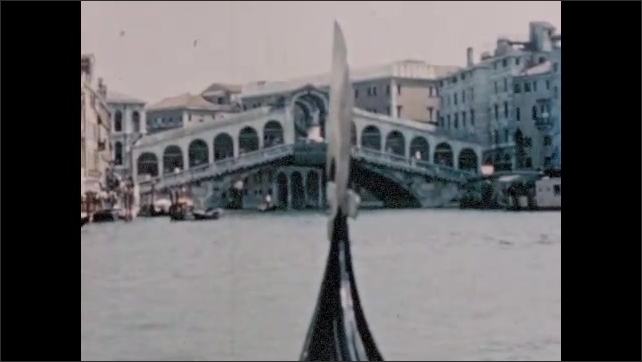 ITALY 1960s: People row gondolas through canals in Venice. Elaborately designed buildings along canal.