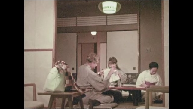 1960s:  View of flowers. Close up of mats on floor. Woman serving man and woman at table.