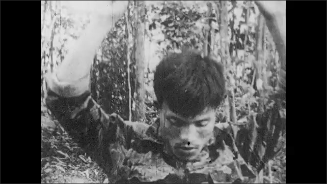 1960s: Man points to map, man plays bugle, Viet Cong soldiers run through jungle, man talks on phone. Man stands with hands raised. Prisoners of war are tied up, connected with rope, march in line.