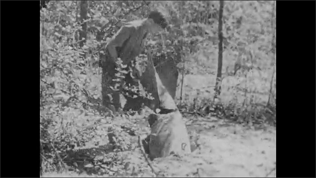 1960s: Vietnamese soldiers run through jungle, branches strapped to backs. Man approaches rocket run into ground. Demolition expert removes bomb from rocket on ground.