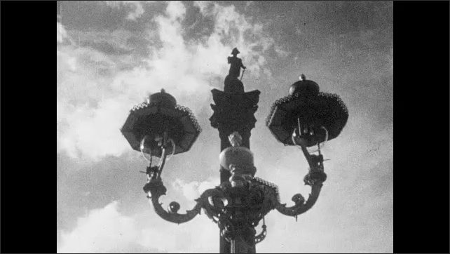1940s: EUROPE: LONDON: Tower Bridge gates open over River Thames. Man smokes pipe on boat. Boats on Thames. Statue of Nelson. Trafalgar Square and Nelson's Column
