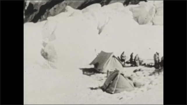 1940s: Climbers ascend mountain. Base camp in snow on Mount Everest. Climbers adjust gear.