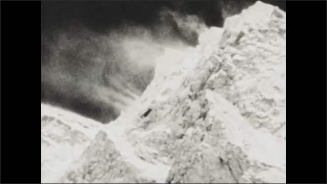 1940s: Wind blows snow on Mount Everest. Climber breathes heavily.
