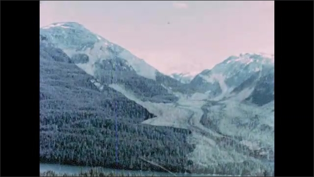 1960s Alaska: Pine forested hills and mountains surround lakes in Alaska. Islands sit in lakes. Snow covered mountains and rivers in Alaska.
