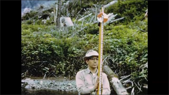 1960s Alaska: Men stand in forest stream and use surveying equipment. Man holds surveying pole. Men survey levels in forest stream. Aerial view of forests and river inlet.