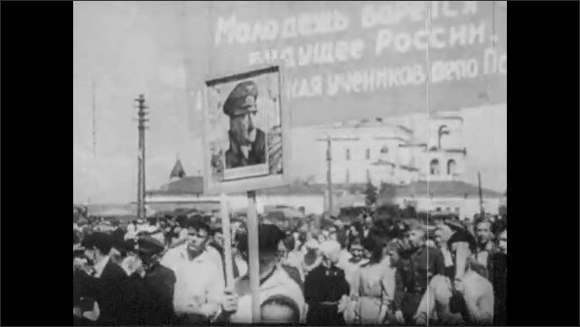 1930s: People hang poster of Adolf Hitler in window. Woman hands out Nazi flags to crowd. People parade through streets. Soldiers march.