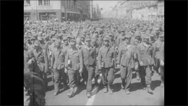 1930s: Man holds white flag.  Large crowd of surrendered soldiers walks down street.  Spectators.