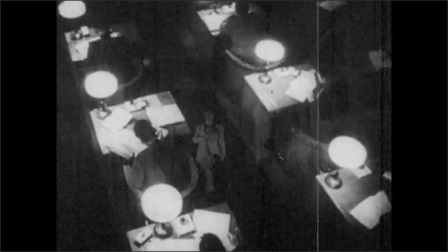 1930s: Statue.  People walk down hallway.  People sit and work at desks.