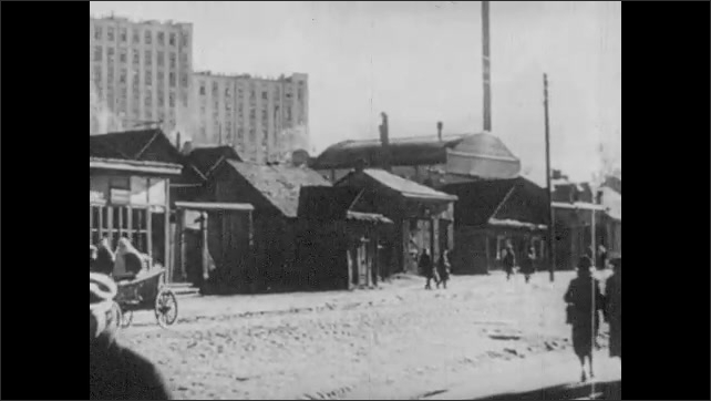 1930s: Buildings.  Shacks.  People walk down city street.  Building with onion domes.