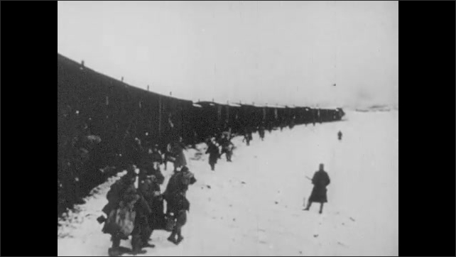 1930s: Train tracks.  Snowy countryside.  Men get off train.  Armed guards.