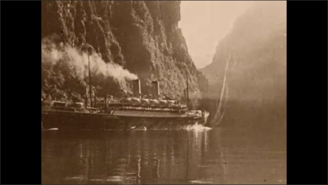 1930s: UNITED STATES: steep cliff by fjord. Steam ship travels along fjord. Boats on water.