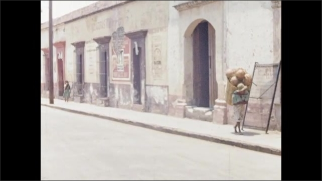 1960s: People walk down side of road in town. People walk down side of road. People sit on side of road with pig.