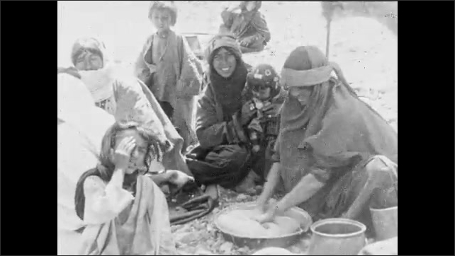 1930s: Intertitle about women making bread. Woman kneads dough in pan as other women and children watch. Woman shapes dough and cooks on fire as men watch.