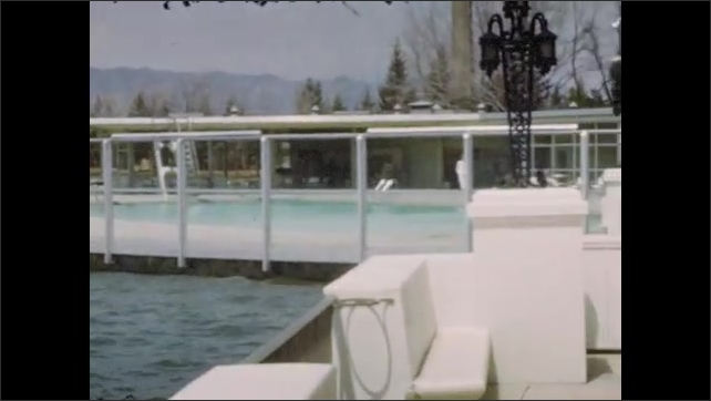1940s:  Exterior of lodge with American flags and cars parked outside. Outdoor pool on a lake. Three adults walk on the patio next to the pool.