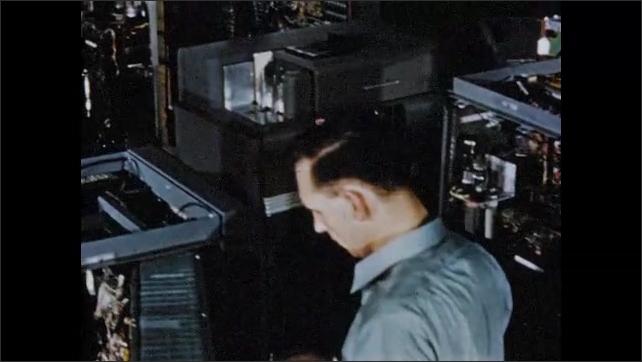 1950s: High angle tracking shot, men assembling computing machines.