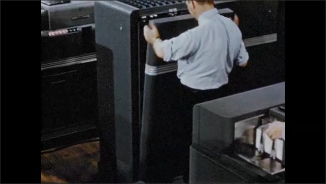1950s: High angle tracking shot, men assembling computing machines. Hand turns page of book, photo of machinery.