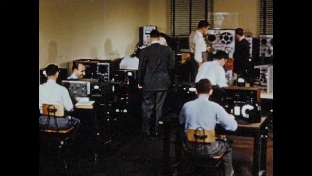 1950s: Computer in room. Men working with electronic equipment. Man working at machine.