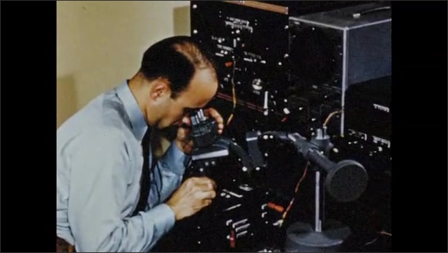 1950s: View through magnifying glass, hands assembling transistor. Man looks through microscope, tracking shot to man working with equipment.