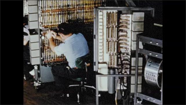 1950s: Tracking shot of men assembling computers.