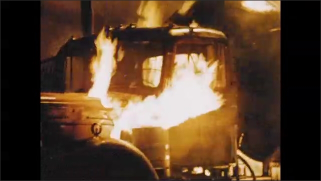 1950s: UNITED STATES: flames under hood of vehicle. Trailer court fire.