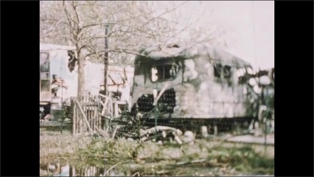 1950s: UNITED STATES: extent of damage to trailers seen in day time. Tank by trailer.