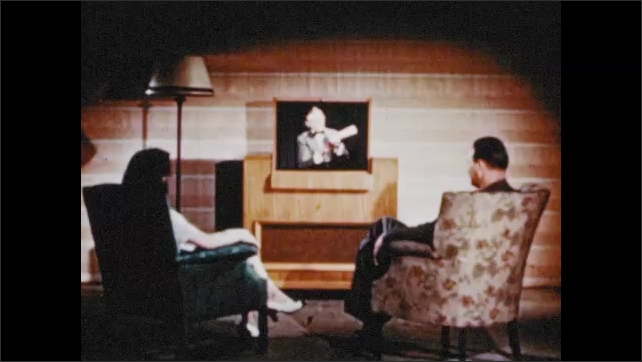 1940s: UNITED STATES: man moves electromagnet. People watch television at home.