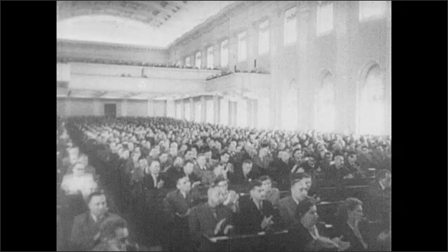 RUSSIA 1960s: Flag with picture of Joseph Stalin. Georgy Malenkov at podium, men clapping in background. Crowd applauding. Malenkov speaking.