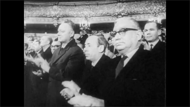 RUSSIA 1960s: Low angle tilt down theater interior, people applauding. Tracking shot of people applauding. Close up of Alexei Kosygin speaking.