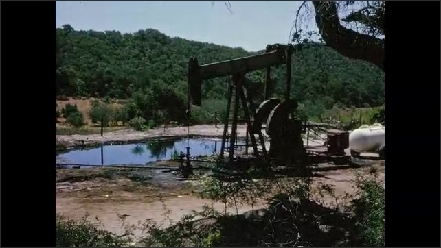 1940s: Woman collects crude oil from pump pipes into glass bottle. Pump jack spins and pumps next to oily pond in the hills of California.