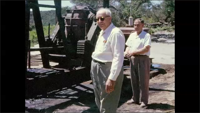 1940s: Men and woman walk around oil pump and talk. Woman leans against oil storage box and nods and motions. Man stands above oil storage box and looks into it.