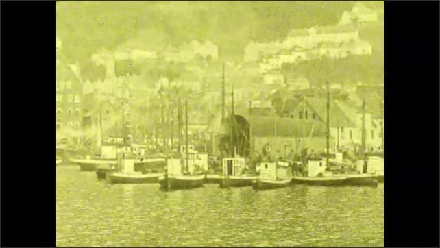 1920s: Boats sit in port near Bergen, Norway. Boats rest at dock near small Scandinavian town. Flag waves near boats. Words on screen.