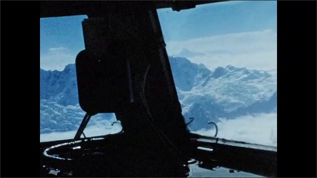 1950s: Plane propeller spins as plane flies through the air. Cockpit of plane, mountains and clouds. Pilot flies plane.
