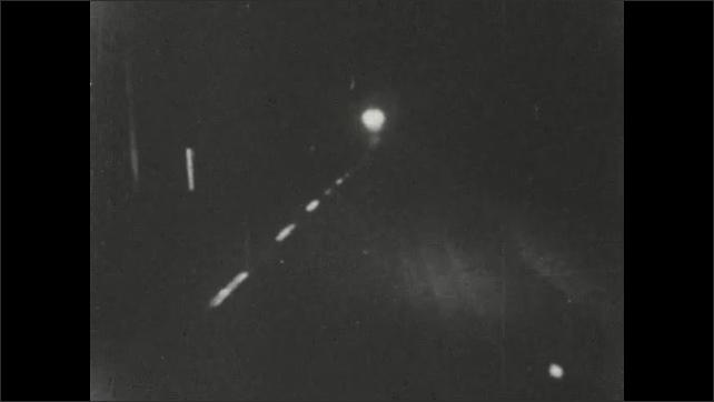 1950s: Driver navigates curvy rural road. Headlights shine and signs reflect on dark road at night.