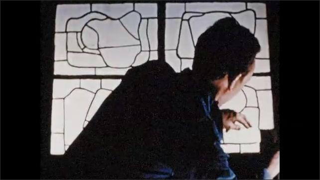 1950s:  Man paints around cut shape on piece of paper.