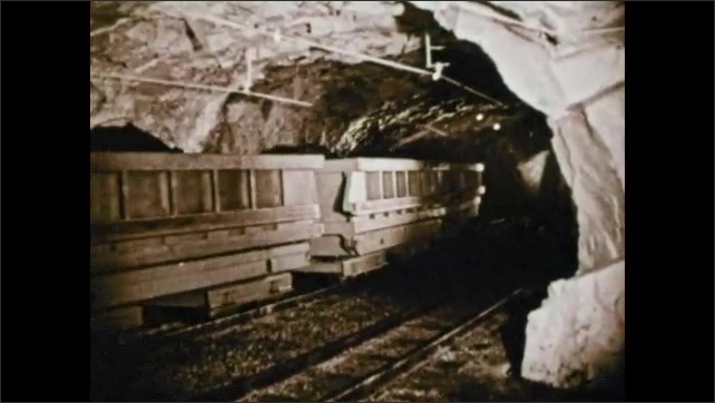 1950s: Men walk through mine tunnel as train car rolls by on tracks. Rocks are carried in cars on tracks. Train goes down tracks carrying cars filled with rocks.