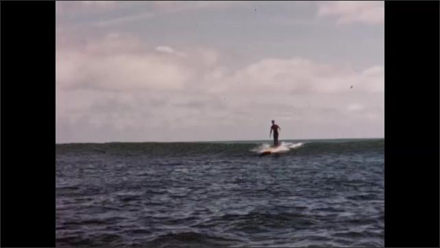 1950s: UNITED STATES: surfers on boards ride wave. Surfing holiday in Honolulu. Hawaii. Man on surf board.