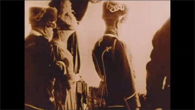 1900s: Women take off in hot air balloon.  Military parade.  Officials stand.  People crouch on field.