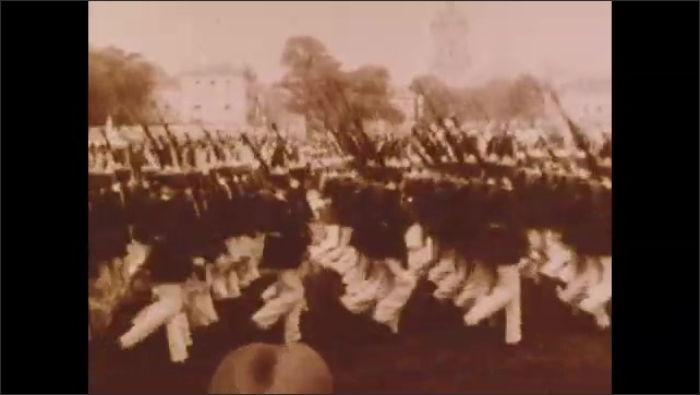 1900s: Dignitaries and officials stand and speak.  Military parade.  Men work in factory.