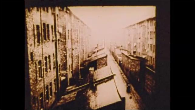 1900s: Industrial plant.  Men walk along.  City.  Smokestacks.  People in yard.  Men on horses in street.