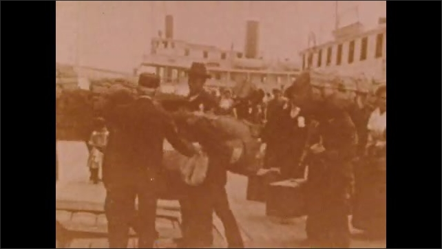 1900s: People on boat.  People carry luggage.  Busy city street.  Outdoor market.