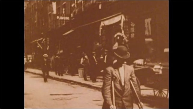 1900s: Busy city market.  One legged man walks down street using crutches.  Men wave from windows.