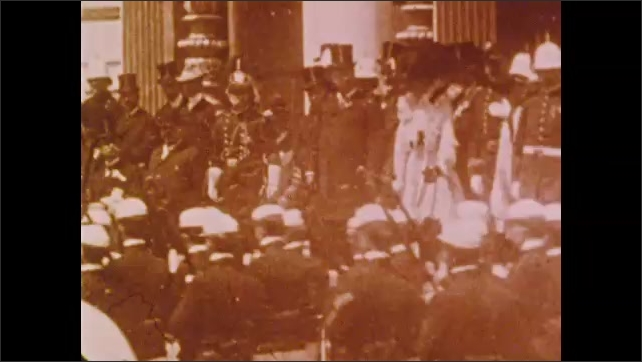 1900s: Busy city street.  Man works in factory.  Parade.  Dignitaries stand on stage.  Policemen.