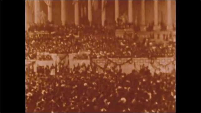 1900s: Man gives speech to crowd.  Parade.