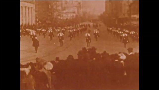 1900s: Parade.  Marchers open umbrellas.  Couples get out of cars and walk.