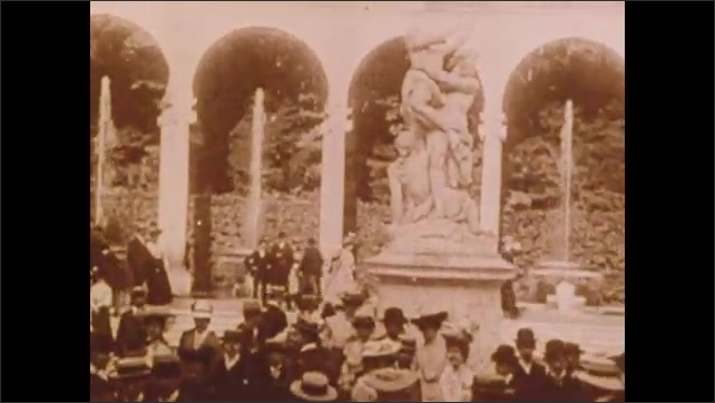 1900s: People in park.  Fountains.  Statues.  Parade.  Car stops in front of dignitaries.